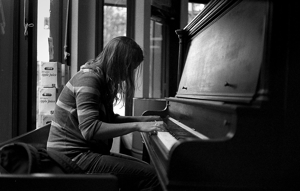 Cafe Pianist - Leica M6, ILFORD HP5+ - This was taken in Ranier Provisions Cafe in Vancouver. It used to be my favorite hang out up until 50 Shades of Grey was filmed there and it became a pitstop for fangirls. I believe they've shut down since. This is a photo of a homeless girl whom the owners gave soup to one cold autumn afternoon. To say thanks, she played the piano... and I sat beside her because... she played beautifully.