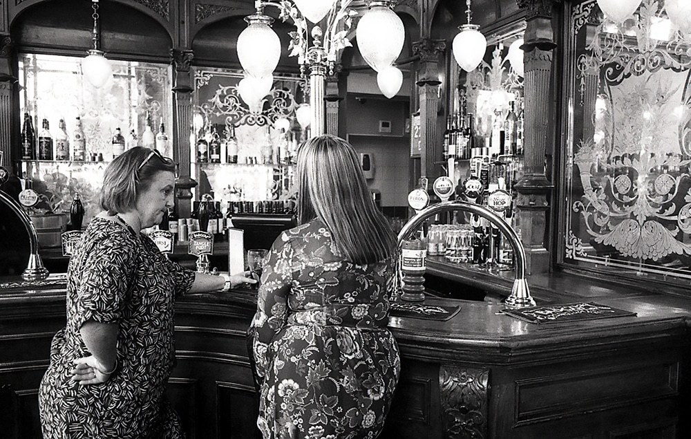 Titas of London - Leica M6, ILFORD HP5+ - This was taken in a pub in London. Two women were gossiping away about their bosses right in front of me, blocking my view of the beer selection. So I stepped back and stole a shot before saying excuse me.