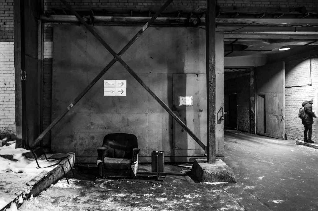 """Getting Closer: Worn armchair and cigarette bin. """"СРЕДА"""" signs overhead and arrows pointing the way."""