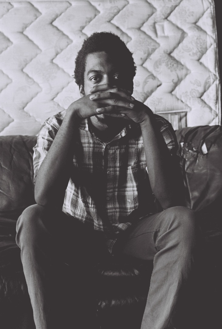 "PORTRAIT - SITTING ON COUCH Mekala Session, known as ""Mickey"" to his friends, sits on his couch in his garage studio. He is a rising drummer synonymous with the LA underground jazz and hip-hop scene, May 2018. Shot on Kodak Tri-X 400."