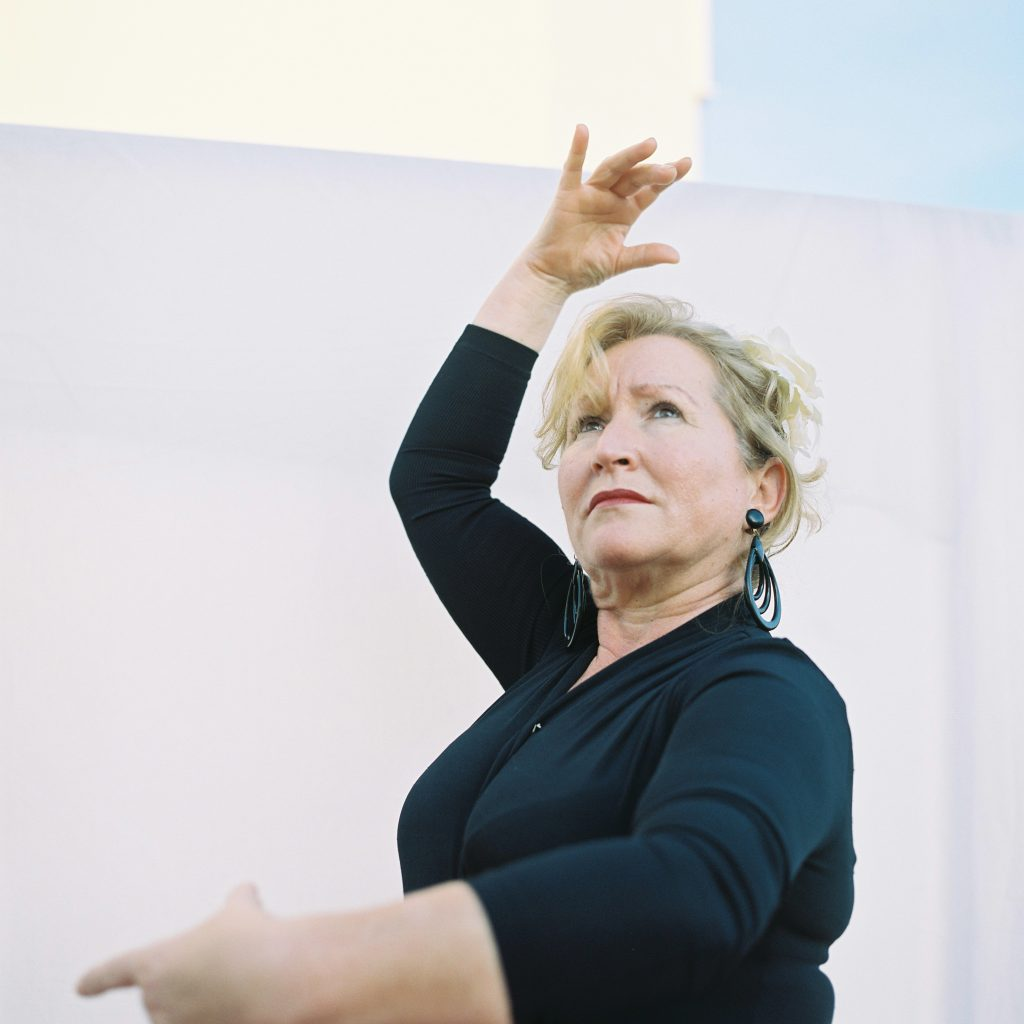 A lady in a black dress holding a dance pose