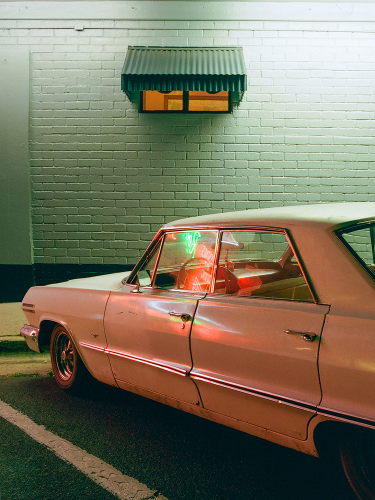 Kyle McDougall - An old car in front of a white painted brick wall