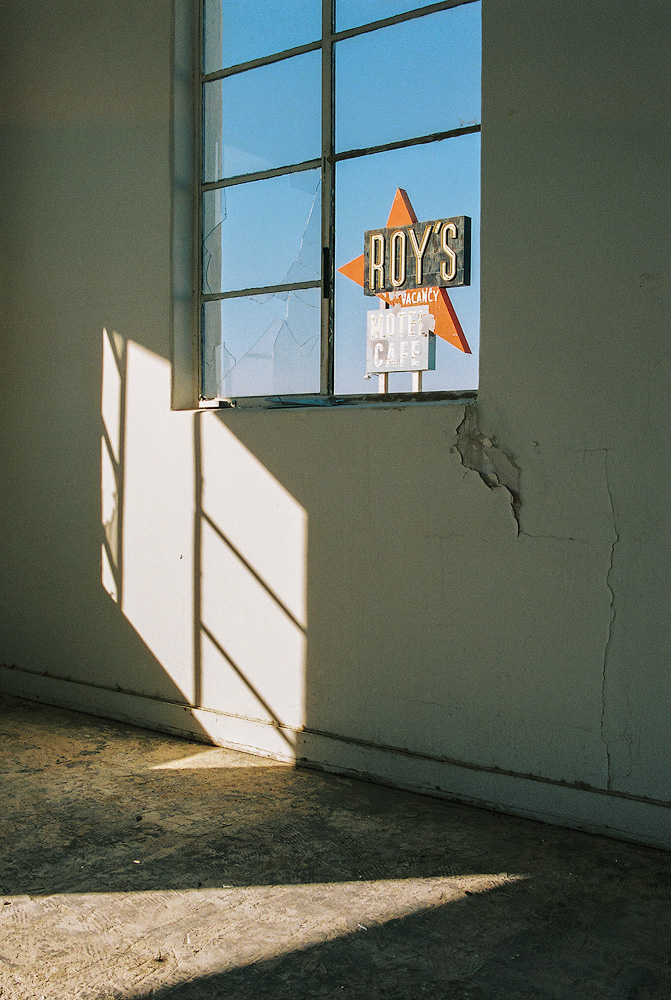 Kyle McDougall - Looking through a broken window in a derelict room and an old road sign