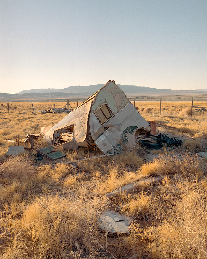 Kyle McDougall - A destroyed caravan in a field with a fence in the background