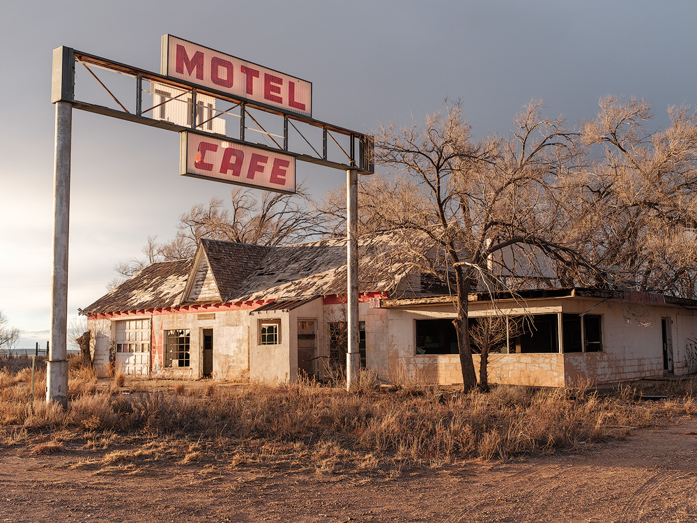 Kyle McDougall - An old isgn reads motel cafe in front of a derelict motel with a tree in front of it