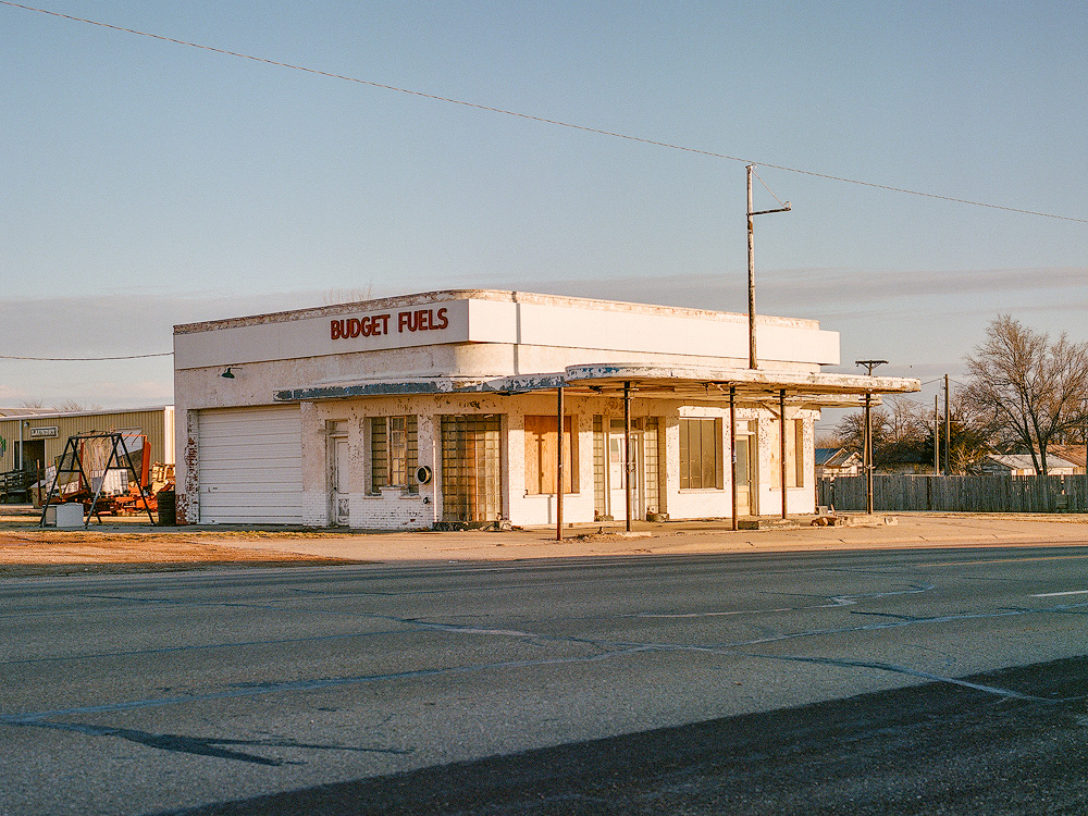 Kyle McDougall - A derelict gas station with a sign saying budget fuels