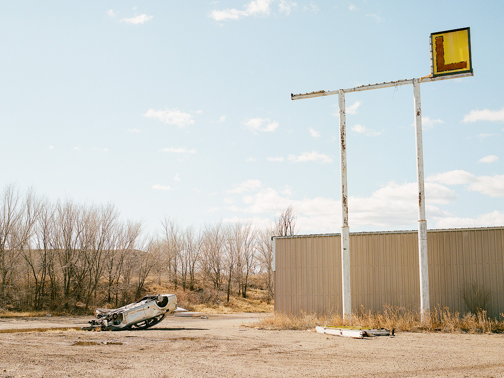Kyle McDougall - A crashed car, upside down in front of a derelict sign