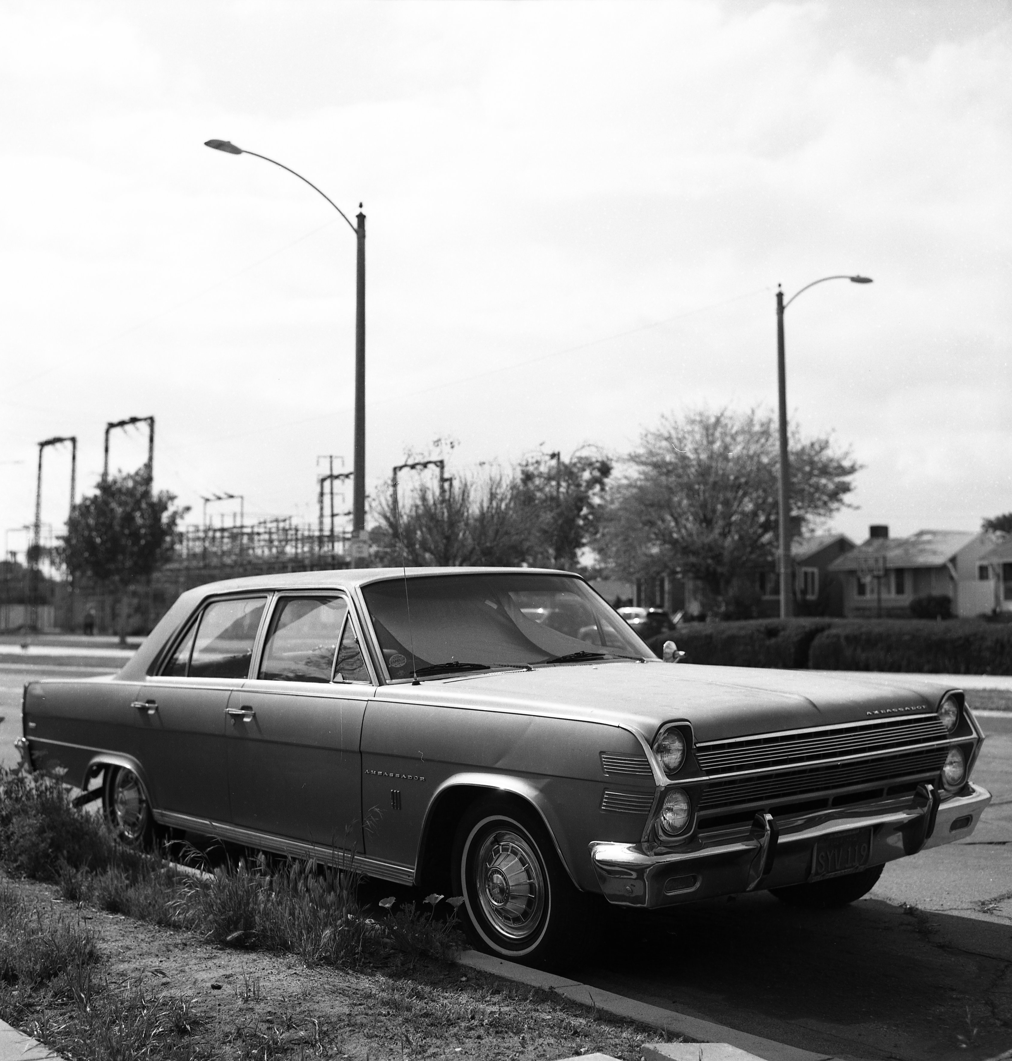 a black and white photograph of an old car by the side of the road
