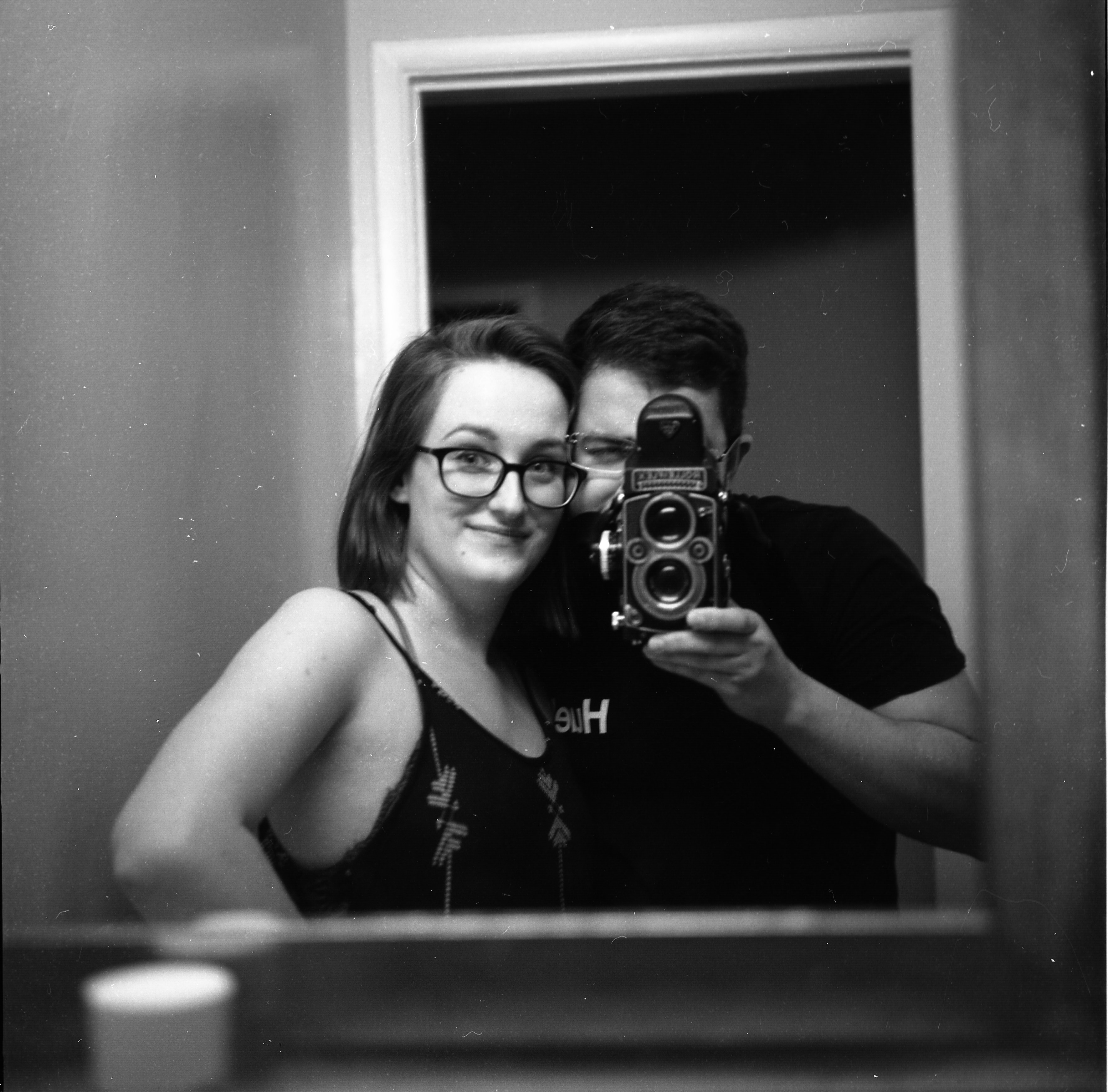 a balck and white selfie of a man and a woman taken in a mirror with a twin lens reflex camera