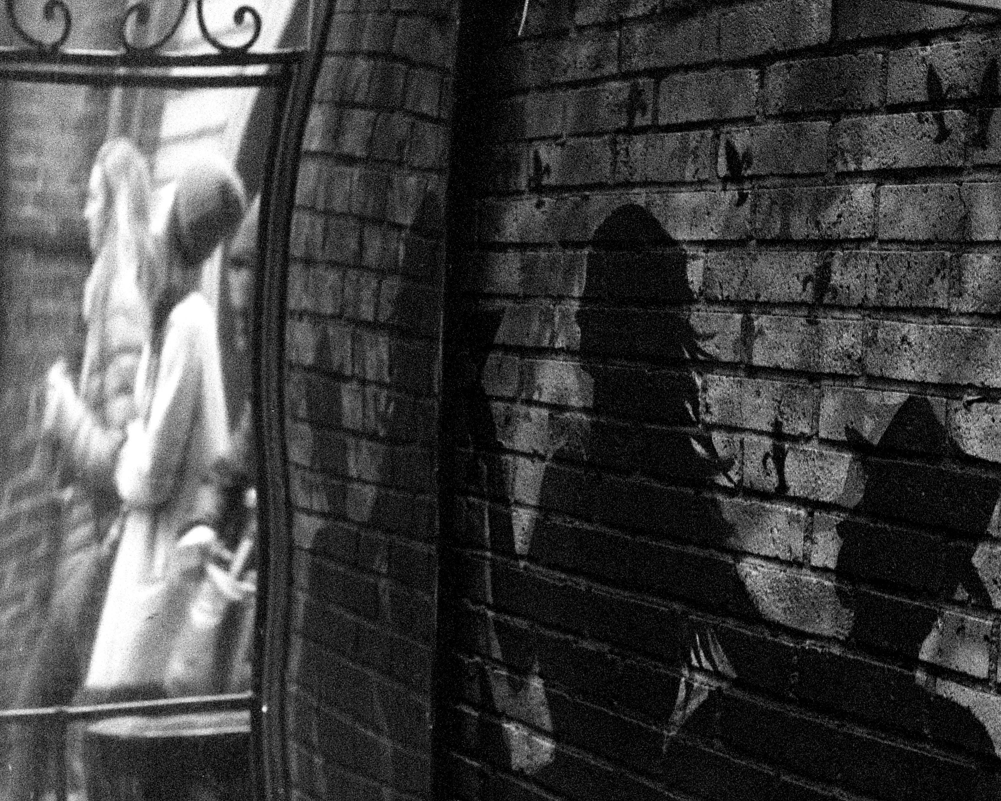 a black and white photograph of a wall and a mirror showing reflections of people