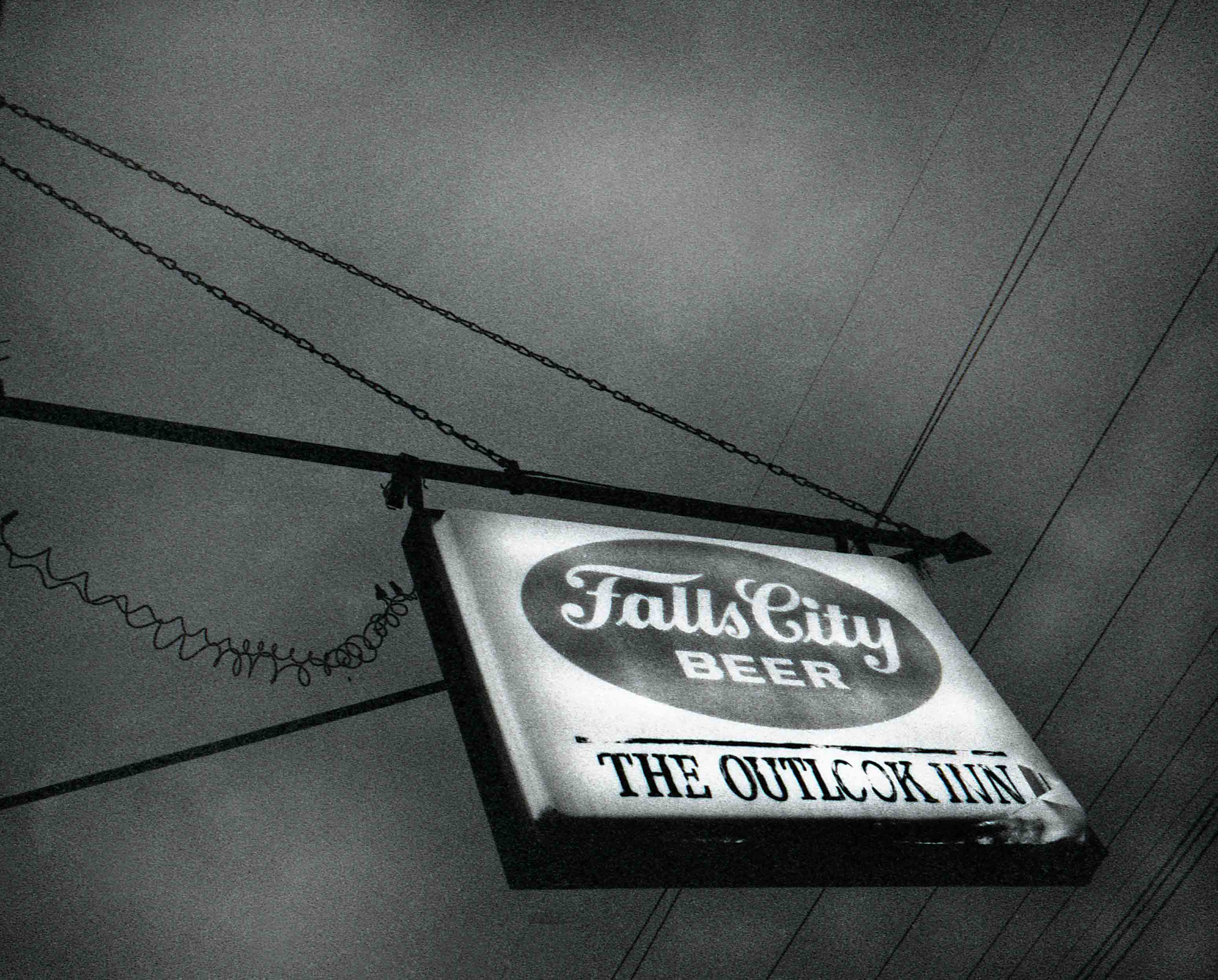 a sign for the outlook inn advertising falls city beer