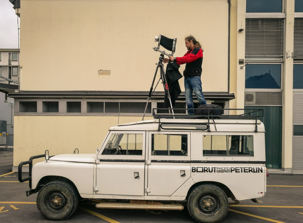 Borut Peterlin on top of his Land Rover with a large format camera