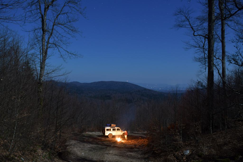 Land Rover beside a campfire at night time