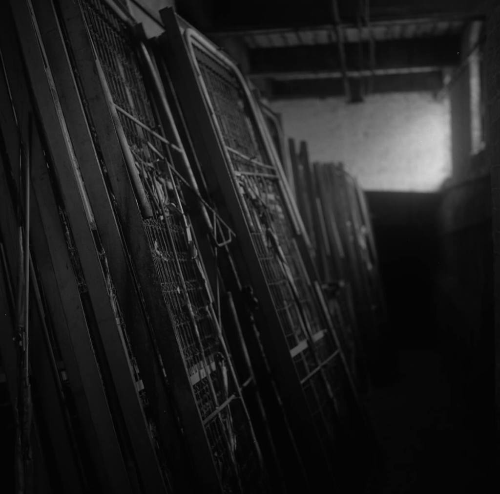 Fujifilm NEOPAN 100 ACROS - The basement of the main building was full of old furniture – filing cabinets, chairs, and old beds stacked up for storage and left to rust.