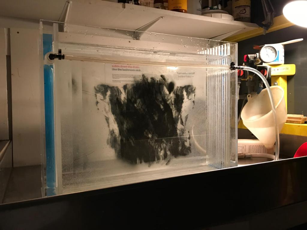 """""""Washing the internegative"""", Several different lith film internegatives rinsing in the print washer during testing."""